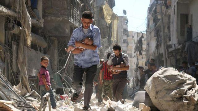 نازح سوري يحمل طفلا
