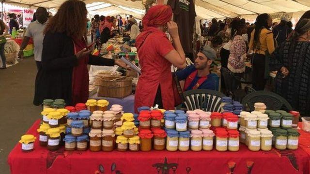 Des clients à l'assaut des produits africains. Du beurre de karité exposé sur une table.