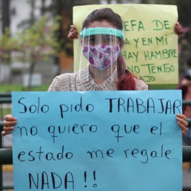 Mujer peruana sostiene cartel pidiendo al gobierno que le permita trabajar