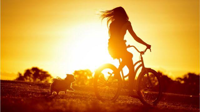 mulher andando de bicicleta com sol ao fundo, e cachorro do lado