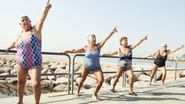 Quatro senhoras com maiô fazem exercício na beira da praia