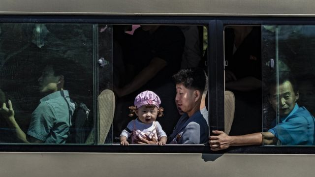 Baby looking out of a Pyongyang bus while her father holds her secure