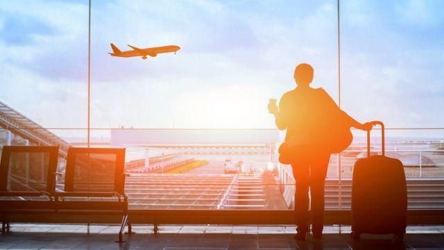 Una mujer en un aeropuerto esperando su vuelo.