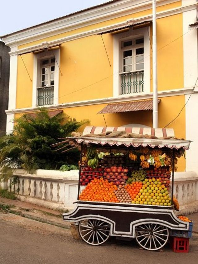 Yellow colonial house with fruit cart - loaded with mangoes - in front.