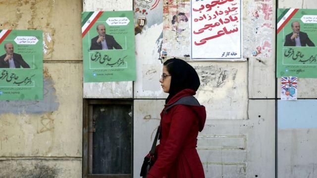 ايرانية تسير قرب ملصق