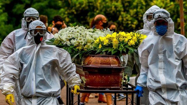 Funcionários paramentados carregam caixão por um cemitério