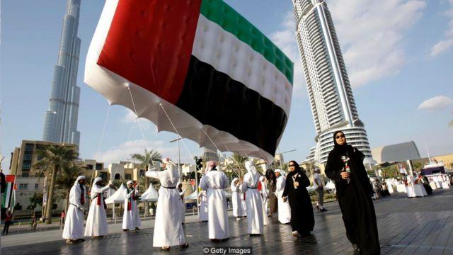 Hombres que llevan una bandera de EAU en una plaza