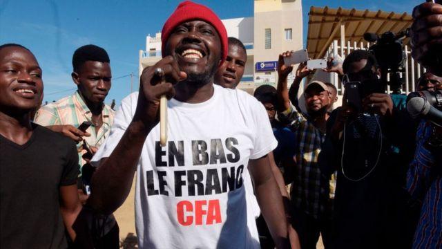 """Activista con camiseta que dice: """"Abajo el franco CFA"""""""