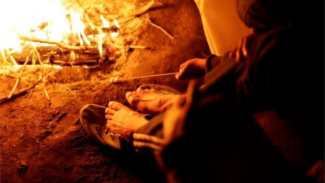 A Mexican man warms himself near a fire as temperatures dropped below freezing in Ciudad Juarez