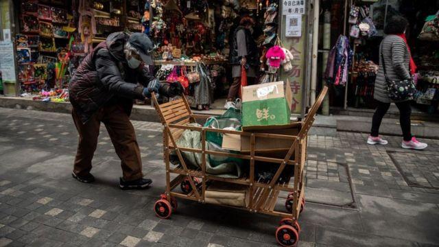 Idosa empurra carrinho com lixo reciclável coletado em Pequim