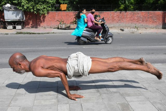 A man practises yoga on a street in Amritsar, India, on 6 October 2021