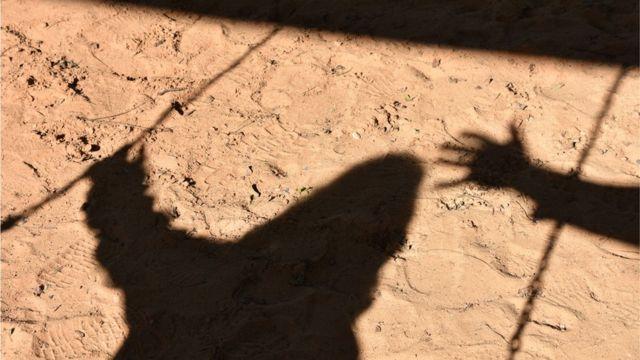 Sombra de una mano acercándose a la sombra de un niño.