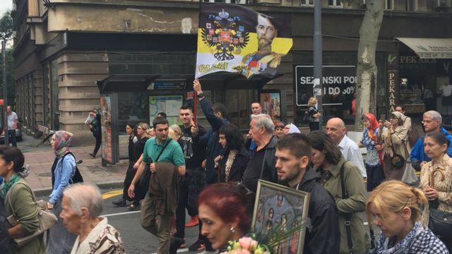 Људи шетају улицом и носе заставу царске Русије
