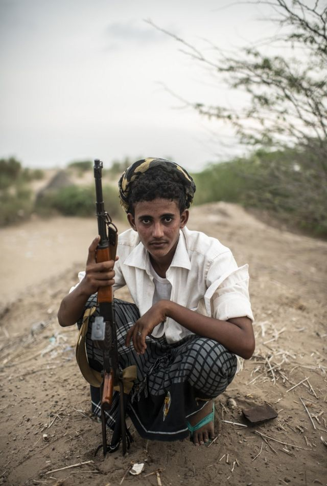 A young man in a Yemen conflict zone crouches whilst holding a gun