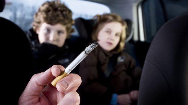 No primeiro plano, uma mão segura um cigarro aceso. No segundo plano, duas crianças - um menino e uma menina - no banco de trás de um carro