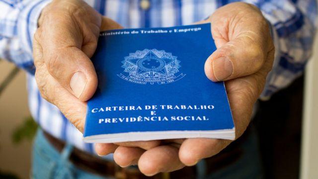 Imagem da carteira de trabalho nas mão de um trabalhador