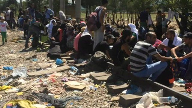 Migrants sitting on train tracks as they wait to be let into Macedonia