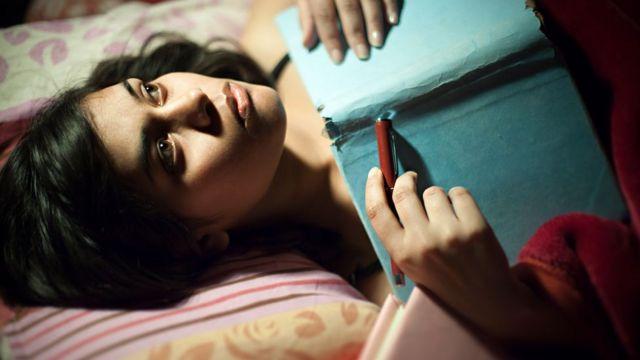 Mulher deitada com caderno na mão
