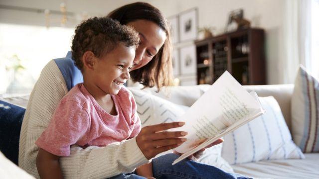 Mãe lendo livro com garoto no colo