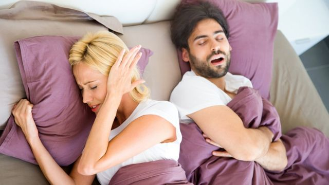 Hombre roncando con su pareja en la cama.