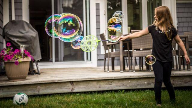 Niña jugando con burbujas de jabón.