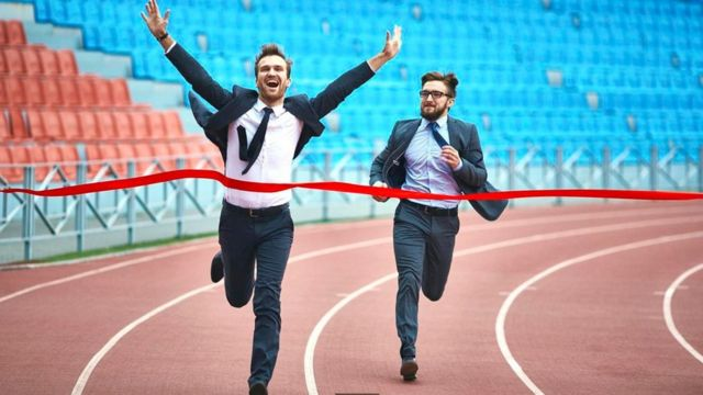 Dos hombres vestidos con traje cruzando la meta en una pista de atletismo