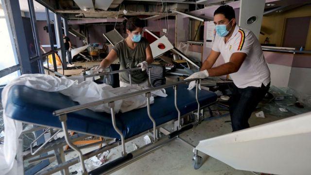 Staff move a gurney in a damaged hospital