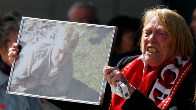 事故で亡くなったキース・マグラスさんの遺影を掲げる遺族