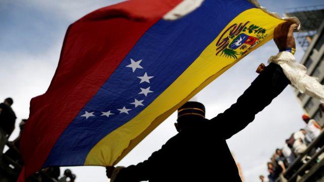 Homem na contraluz ergue bandeira da Venezuela em uma rua, em dia de sol