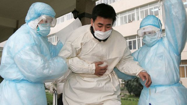 Paciente siendo aislado por personal médico en China en 2003.
