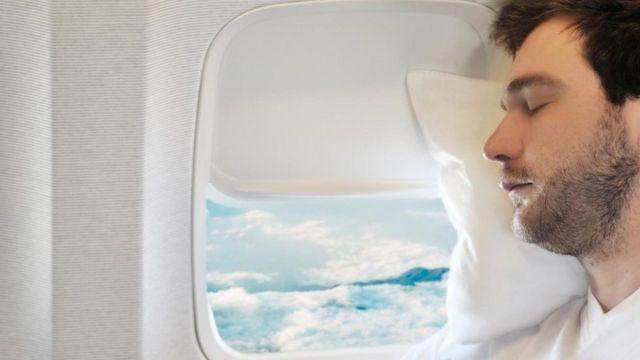 Un hombre durmiendo en un avión