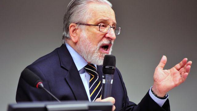 Roberto Abdenur fala no microfone em ambiente interno, sentado, e gesticulando com uma das mãos