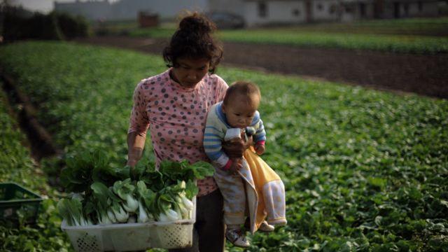 Mãe com bebê em área rural da China