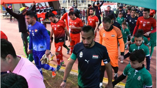 Players make their way on to the field from the sidelines before the game
