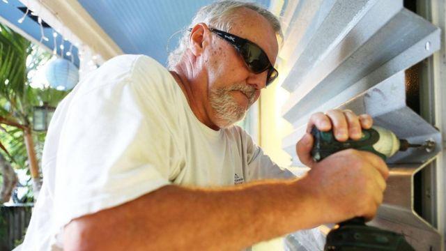 أحد سكان مدينة إسلامورادا في ولاية فلوريدا يركب مصراعا للحماية من الأعاصير