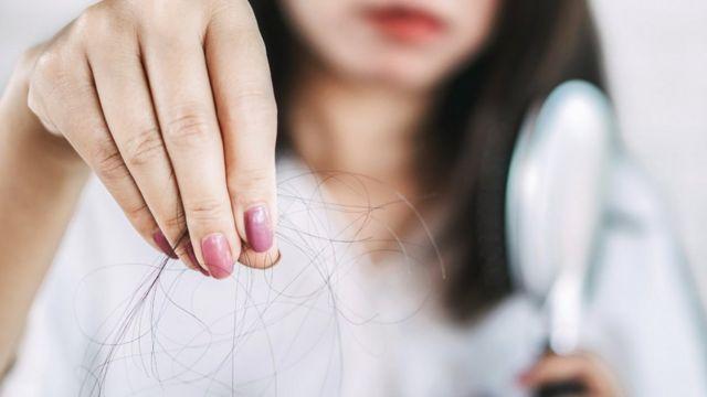Una mujer sosteniendo unos cabellos en la mano.