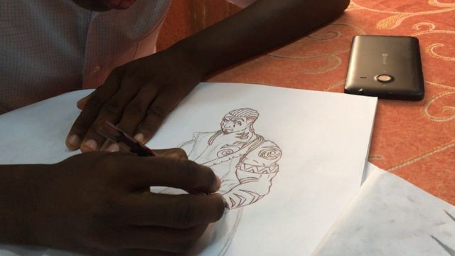 A pair of hands drawing a comic character