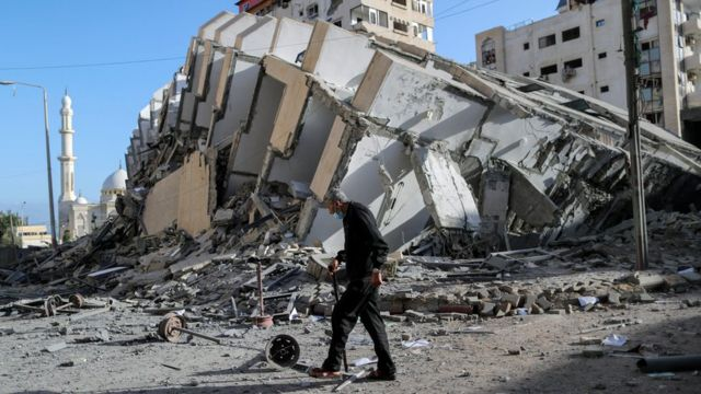 A Palestinian man walks past the remains of a tower block in Gaza City that was destroyed in an Israeli air strike (12 May 2021)