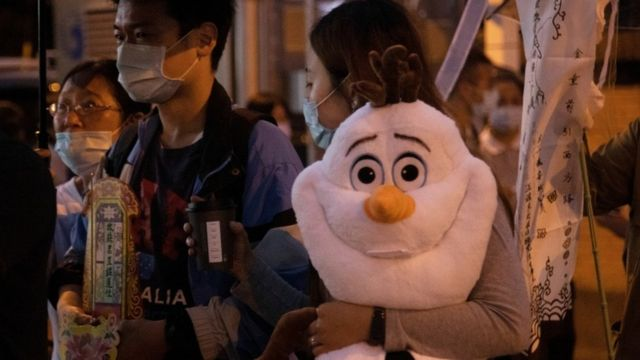 A woman holding a stuffed Olaf toy