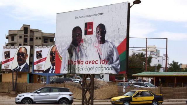 Des voitures passent sous les pancartes de campagne des candidats à la présidentielle au Sénégal.