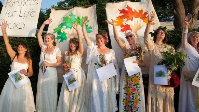 نساء يرتدين فساتين زفاف ويحملن باقات ورود