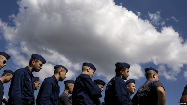 Hungarian police at a reception camp for migrants