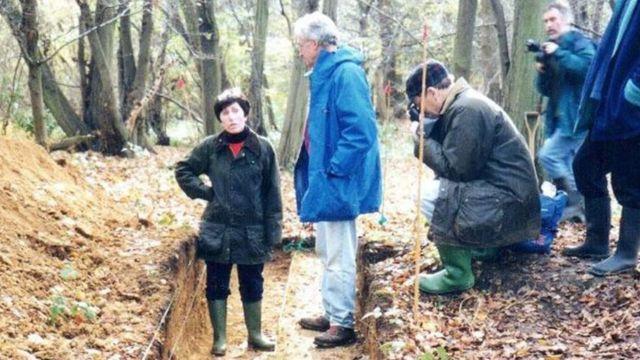 A professora Patricia Wiltshire entre quatro homens fotografando no meio da floresta