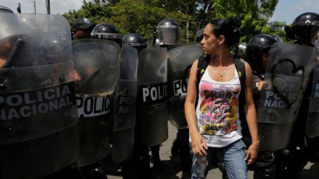 Mujer pasa frente a efectivos de policía