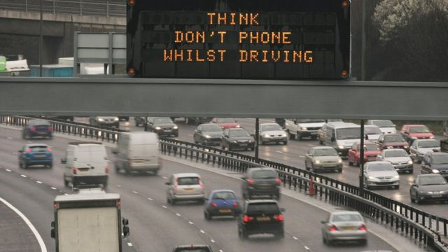 'Think Don't Phone Whilst Driving' sign on motorway