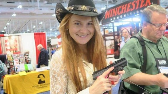 Butina sosteniendo una pistola.