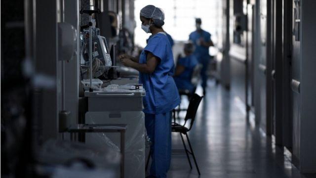 Três profissionais de saúde em corredor de hospital