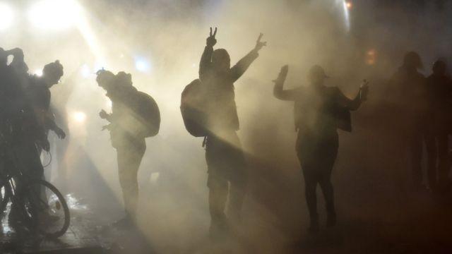 漢堡街頭一批示威者在水霧中舉起勝利手勢(8/7/2017)
