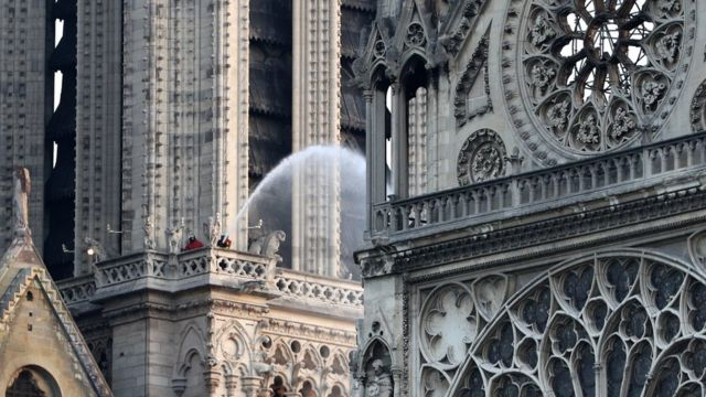 Firefighters hose down Notre-Dame cathedral after a fire tore through the ancient building, April 2019