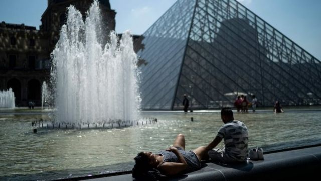 People sunbath in front of the Louvre Pyramid (Pyramide du Louvre) during a heatwave in Paris
